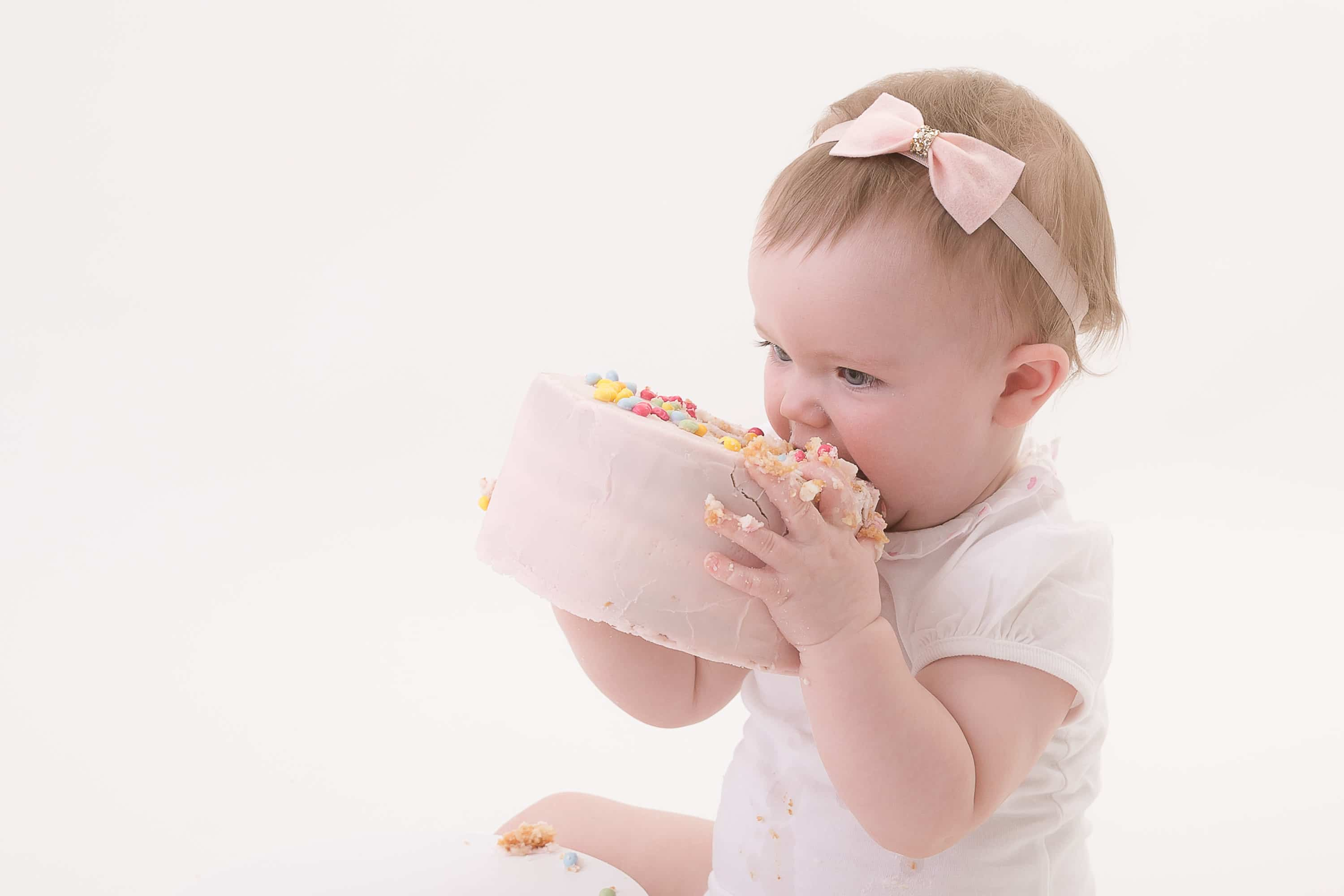 baby eating a big cake