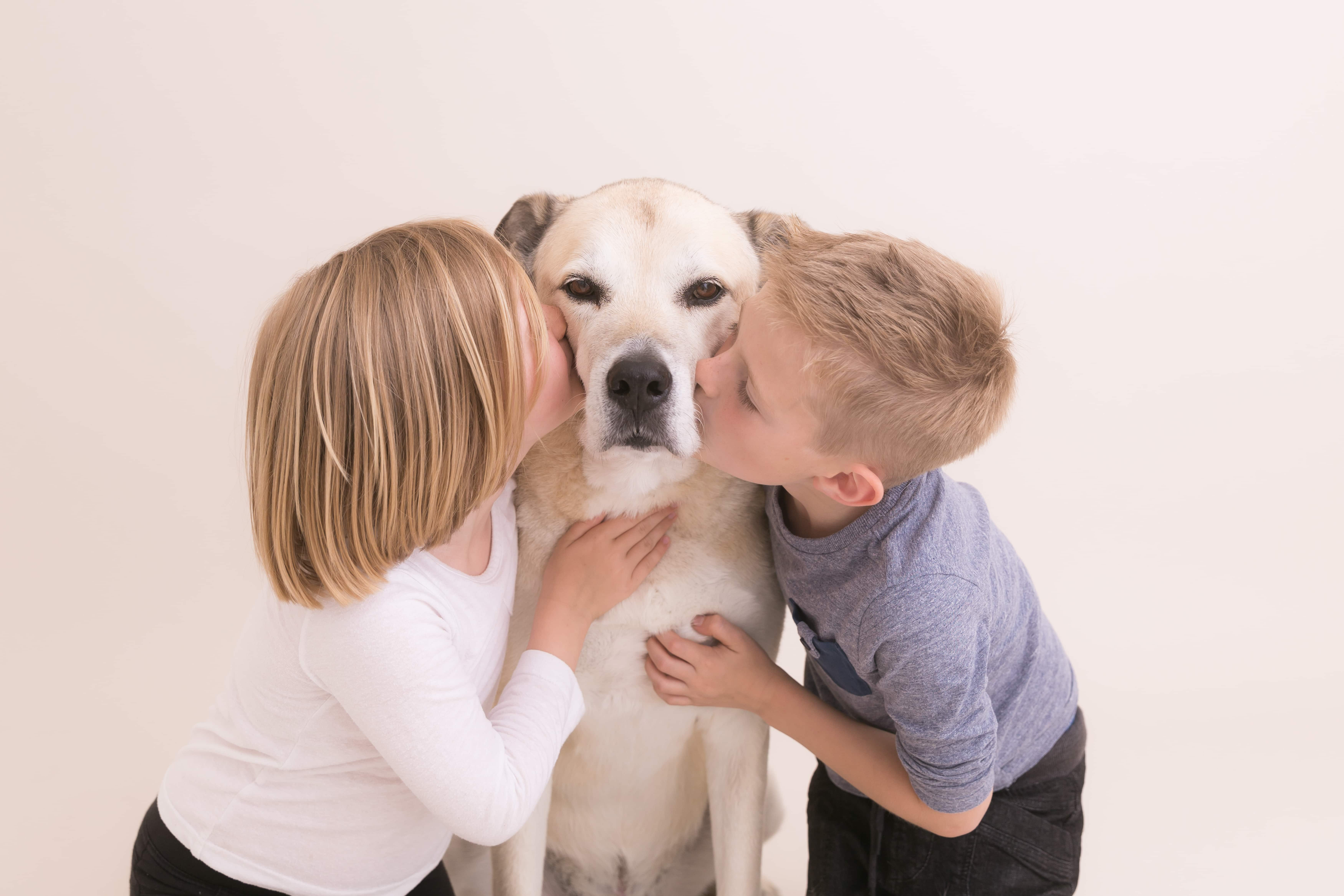 dog being kissed by two children